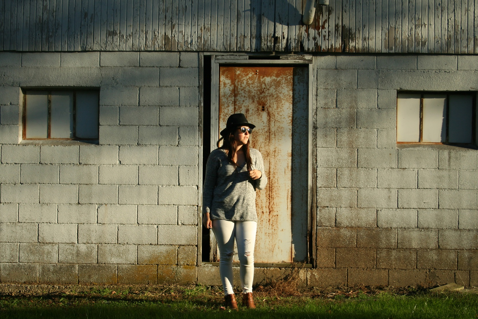 black panama hat, marled sweater, white jeans and a cognac boot